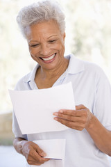 Woman reading letter smiling