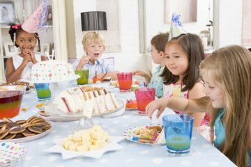 Young children at party sitting at table with food smiling