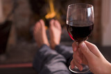 Feet warming at fireplace with hand holding wine