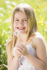 Young girl sitting outdoors holding dandelion head smiling