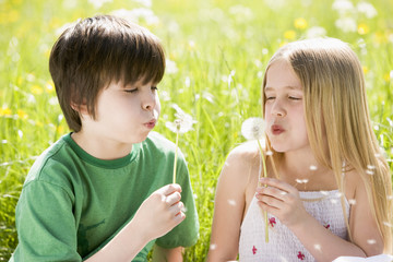Two young children sitting outdoors blowing dandelion heads smil