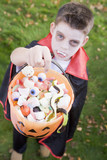 Young boy outdoors wearing vampire costume on Halloween holding