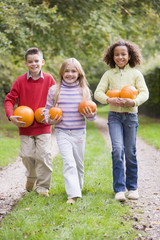 Three young friends walking on path with pumpkins smiling