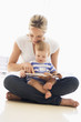 Mother and baby indoors reading book and smiling