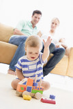 Fototapety Couple in living room with baby smiling