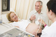 Pregnant woman getting ultrasound from doctor with husband watch