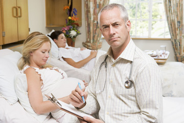 Doctor sitting by pregnant women holding chart