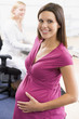 Pregnant woman at work holding belly smiling