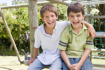 Two young male friends at a playground smiling