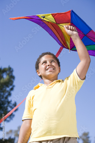 Young boy with kite outdoors smiling