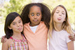 Three young girl friends outdoors making funny faces