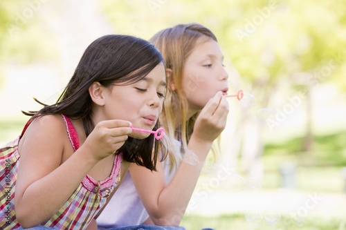 Two young girls blowing bubbles outdoors