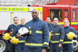 Portrait of a group of firefighters by a fire engine - 8652496