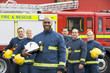 Leinwanddruck Bild - Portrait of a group of firefighters by a fire engine