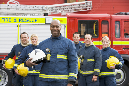 Portrait of a group of firefighters by a fire engine - 8652498