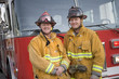 Portrait of two firefighters by a fire engine - 8652871