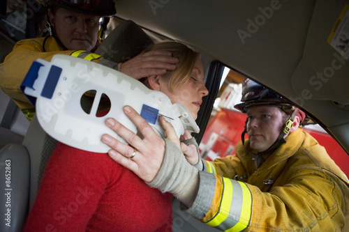 Firefighters helping an injured woman in a car - 8652863