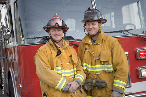 Portrait of two firefighters by a fire engine