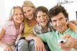 Family in living room with remote control smiling