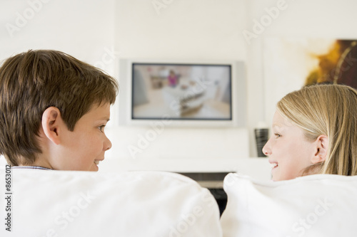 Young boy and young girl in living room with flat screen televis