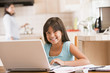 Young girl in kitchen with laptop and paperwork smiling with wom