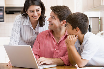 Family in kitchen with laptop smiling