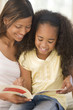 Woman and young girl sitting in living room reading book and smi