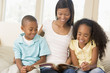 Woman and two children sitting in living room reading book and s