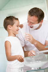 Man in bathroom putting shaving cream on young boy's nose