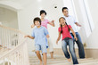 Family running down staircase smiling
