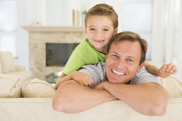 Man and young boy sitting in living room smiling