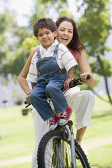 Woman and young boy on a bike outdoors smiling
