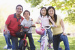 Family with children on bikes outdoors smiling