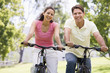Couple on bikes outdoors smiling - 8654424