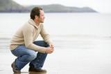 Fototapety Man crouching on beach