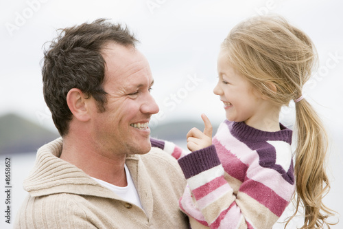 Father and daughter at beach smiling