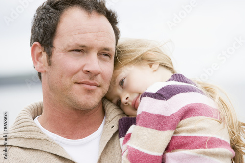 Father holding daughter at beach