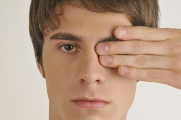"""Young male adult;hand covering one eye"""