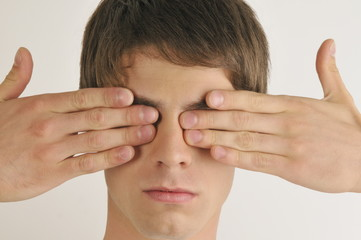 """Young male adult;hands covering eyes"""