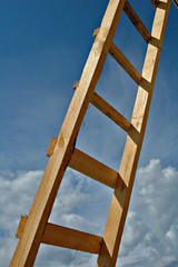 New wooden ladder on a background of the sky with clouds.
