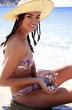 Young woman in bikini and hat on beach