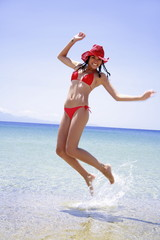 Young woman in bikini and hat jumping in the air