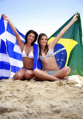 Young women on beach holding up flags