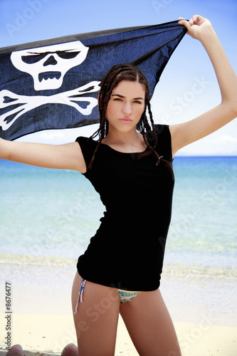 Young woman in bikini holding up skull and bones flag