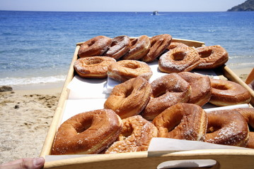 A tray of donuts on the beach