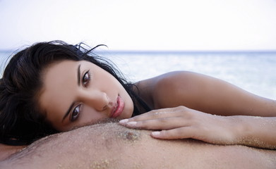 Young woman on man's chest on beach