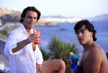 Two men toasting with cocktails by the seaside