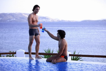 Two men toasting with cocktails by the poolside
