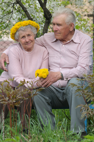 happy old couple against a background of flowering garden with d