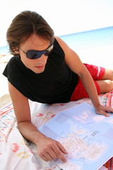 Young man on beach reading map